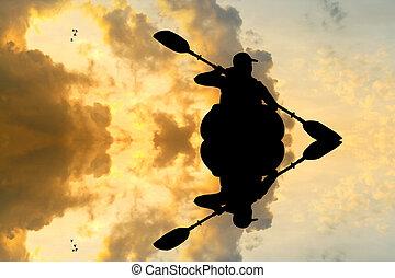 man with a kayak at sunset