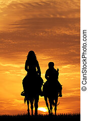 mother and child on horse at sunset