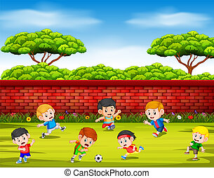 the children playing soccer with their team together in the yard