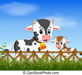 the natural view with the cow and her little cow playing together with the happy face