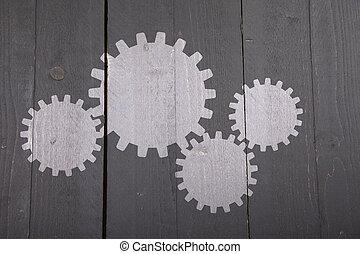 Illustration of white gears on dark black wooden background