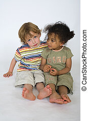 A young blond boy and a beautiful mixed race little girl sit together, with concerned looks.