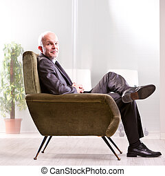 Mature businessman sitting on a very comfortable armchair relaxing and smiling at you