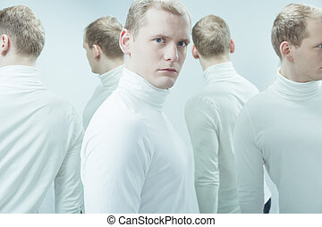 Duplicated image of man with mental problem, standing in white interior