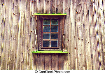 carved frame and window in the old wooden house from boards