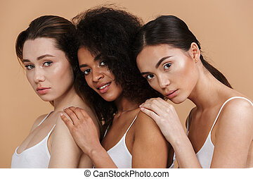 Image closeup of three gorgeous women of different nation: caucasian, african american and asian girls in basic clothing, standing together isolated over beige background