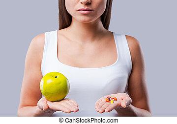 image, femme, ton, pomme, elle, faire, jeune, tondu, choice!, tenant mains, pilules