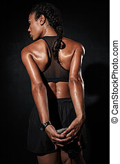 Image from back of african american woman in sportswear doing workout