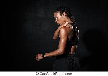 Image from back of feminine african american woman in sportswear