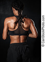 Image from back of muscular african american woman in sportswear