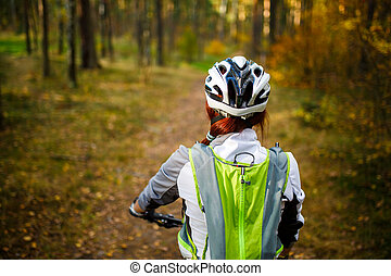 Image from back of woman in helmet on bicycle in autumn...