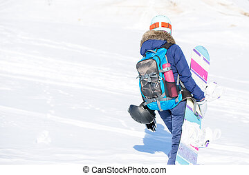 Image from back of woman in helmet with backpack and snowboard