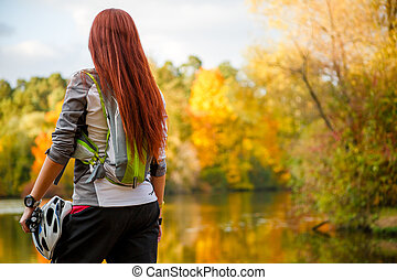 Image from back of woman with backpack and bicycle helmet...