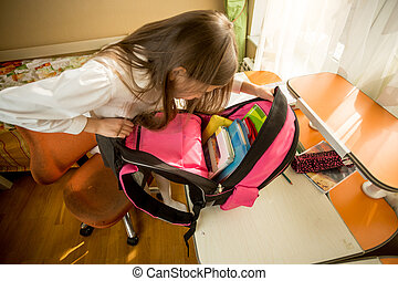 Image from high point of cute schoolgirl looking inside of...