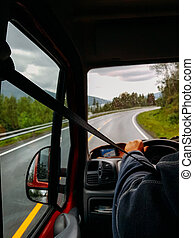 Image from passenger compartment of car driving along road among green trees in Norway on summer.