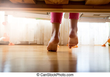 Image from under the bed on girl stepping on wooden floor at...