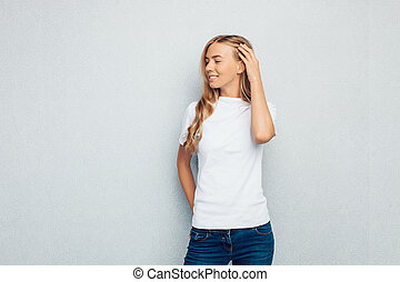 Image of a beautiful girl dressed in a white t-shirt standing against a gray wall posing.