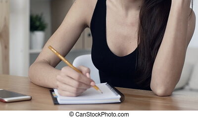 Image of a frustrated or tired young brunette woman with notepad at the office rubbing temples