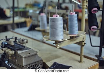 Image of a lot of coils with a threads at the sewing workshop.