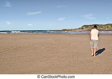 man on phone on beach