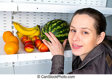 Image of a woman buying fruits in a market.