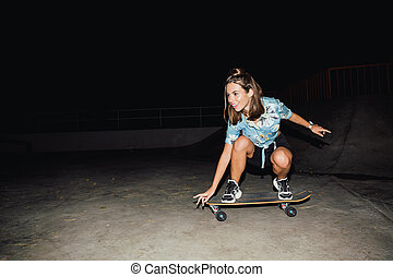 Image of adorable caucasian girl smiling and riding skateboard at night