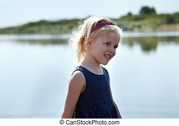 Image of adorable little girl on lake background