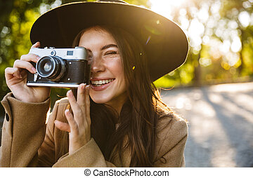Image of adorable woman taking photo on retro camera outdoors