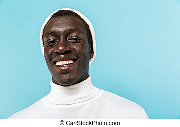 Image of african american guy in white clothes smiling at camera