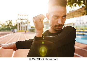 Image of african american man in sportswear doing workout outdoors