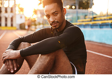 Image of african american man sitting at sports ground outdoors