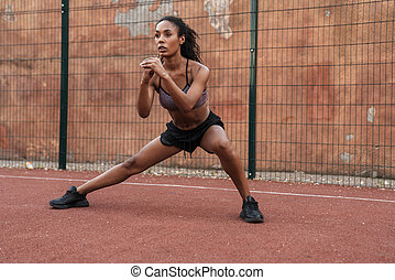 Image of african american woman doing workout at playground outdoors
