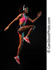 Image of african american woman in headphones jumping while working out