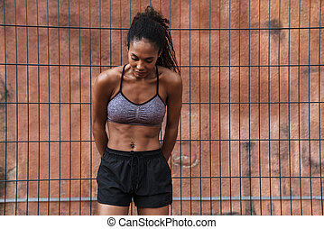 Image of african american woman in sportswear standing at playground