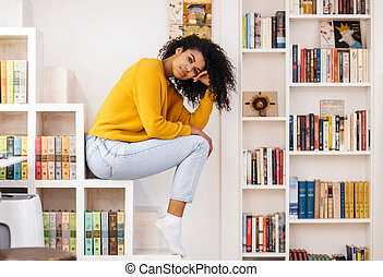 Image of african american woman looking at camera while sitting on shelf