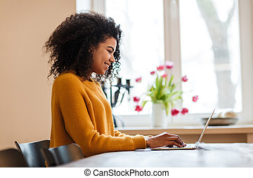 Image of african american woman using laptop while sitting at table