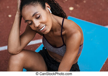 Image of african american woman with earbuds sitting at playground