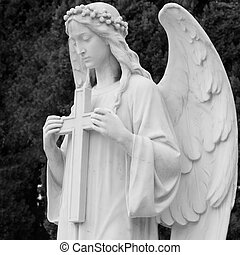 image of angel holding a cross - detail of historic tomb on ...