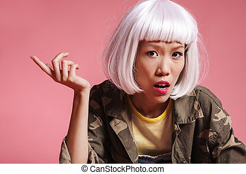 Image of asian girl wearing wig resenting and gesturing in ...