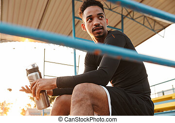 Image of athletic african american man sitting at sports stadium outdoors