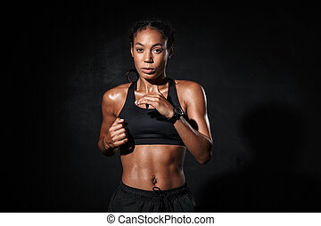 Image of athletic african american woman in sportswear doing workout