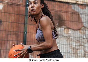 Image of athletic african american woman playing basketball at playground