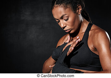 Image of athletic african american woman wearing boxing hand wraps