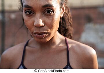 Image of attractive african american woman standing at playground