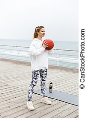 Image of attractive athletic woman doing exercises with fitness boll while working out near seaside
