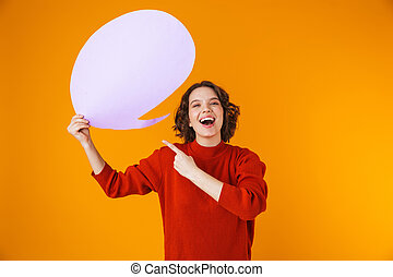 Image of attractive girl holding thought bubble with copyspace while standing isolated over yellow background