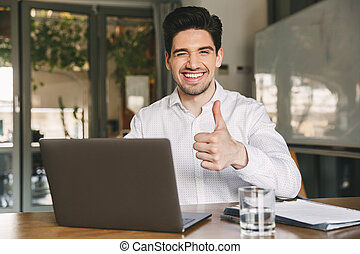 Image of attractive smiling office guy 30s wearing white shirt winking and showing thumb up at camera, while sitting and working on laptop
