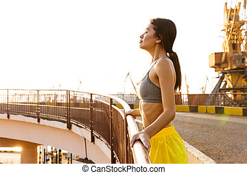Image of beautiful asian woman standing over railing at sea port