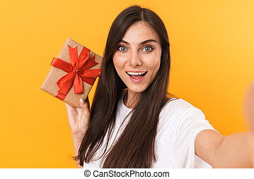 Image of beautiful brunette woman with long hair holding present box while taking selfie photo