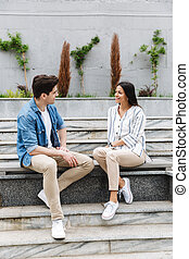Image of beautiful couple talking and smiling while sitting on bench near stairs outdoors